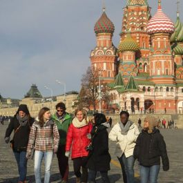 "A ""Comrade Group"" walks to the Kremlin with St. Basil's Cathedral in the background"